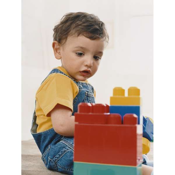small child looking at large lego blocks not playing with them