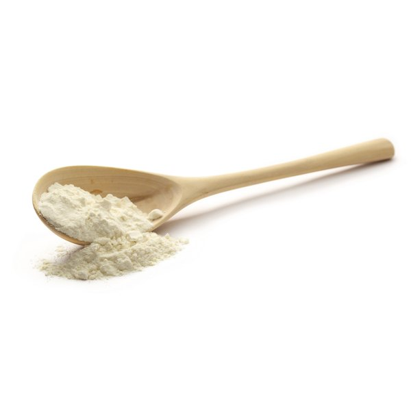 A wooden spoon of potassium lactate on a white counter.