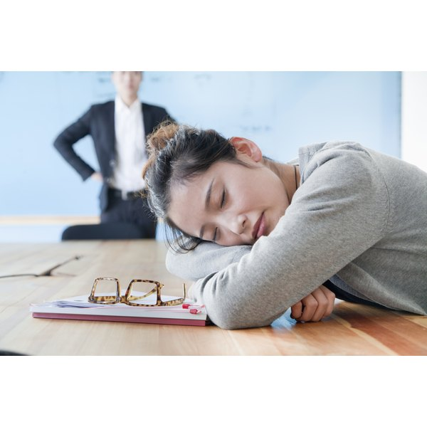 An exhausted woman is lying her head down on a conference table.