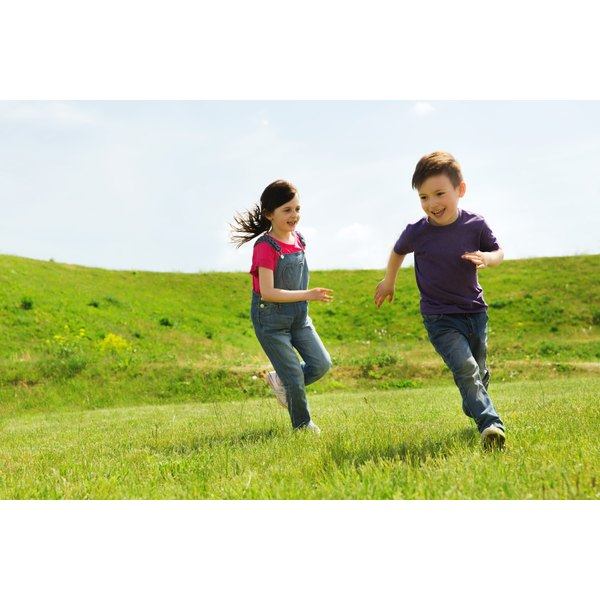 Two eight year-olds play tag in a hilly grassed park.