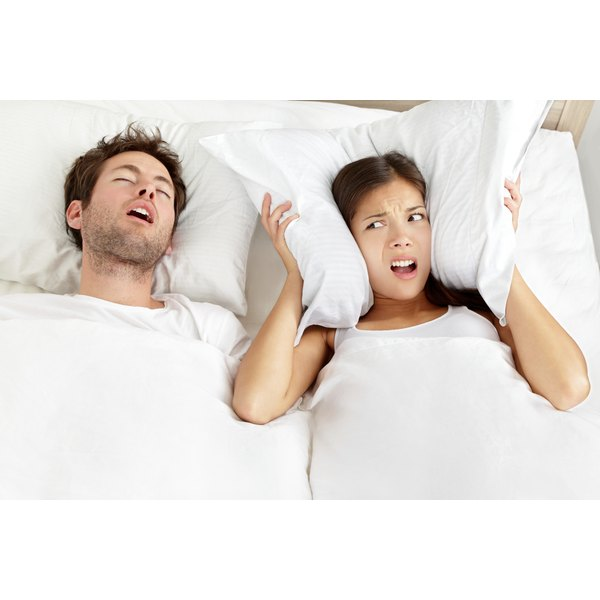 A couple in bed with the man snoring and the woman covering her ears with a pillow.