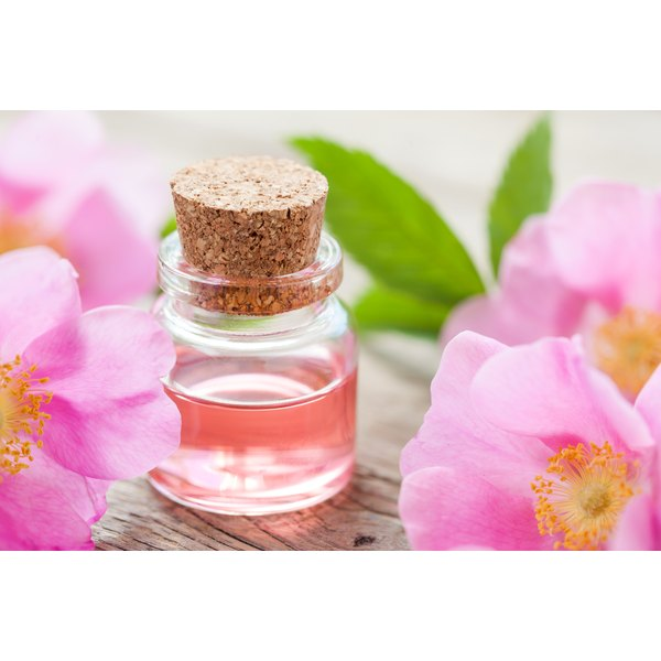 A bottle of rose hips oil on a table with rose blooms.