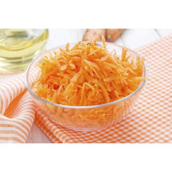 A glass bowl of grated carrots on a tea towel.