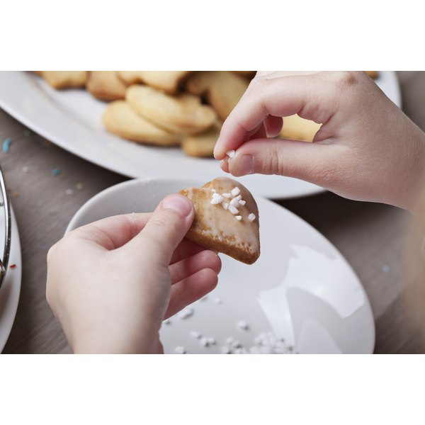 A close-up of a child sprinkling sugar onto a cookie.