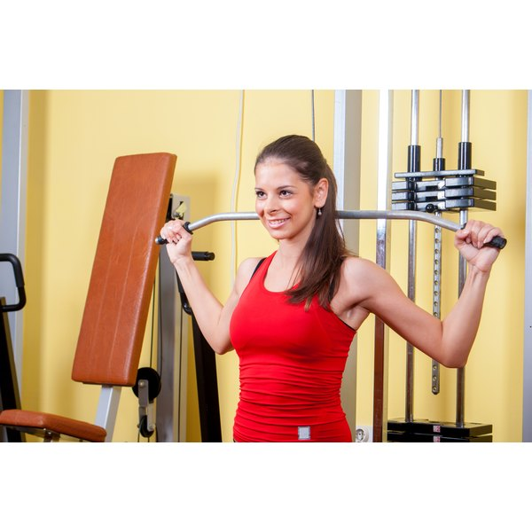 A young woman is doing lateral pull downs.