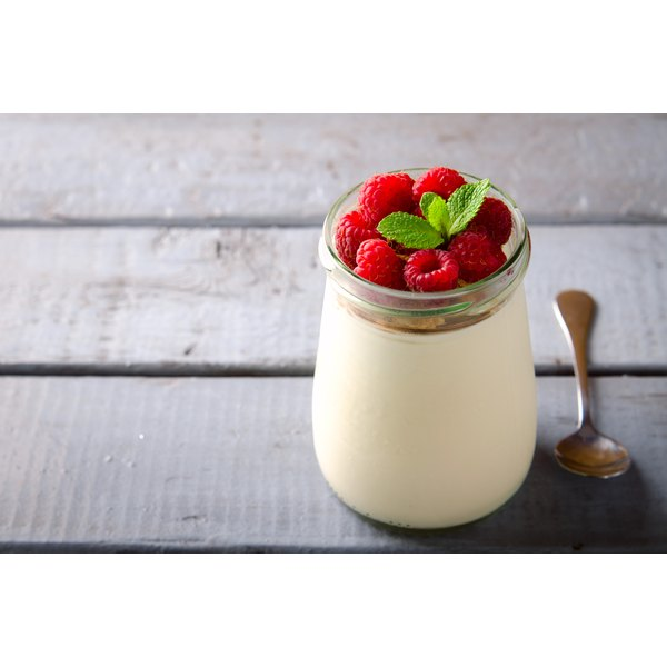 A jar of yogurt with with raspberries on a wooden table.