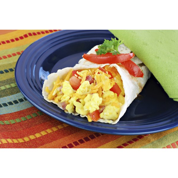 A breakfast burrito with eggs and salsa on a plate.