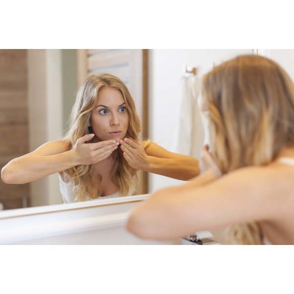 A woman is popping a pimple in the mirror.