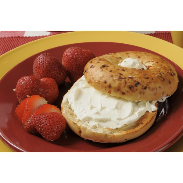 An onion bagel with cream cheese and berries.