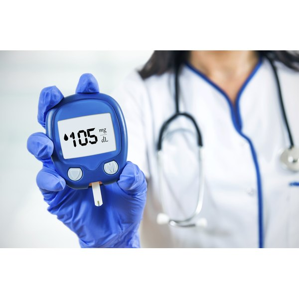 A doctor is holding up a blood glucose monitor.