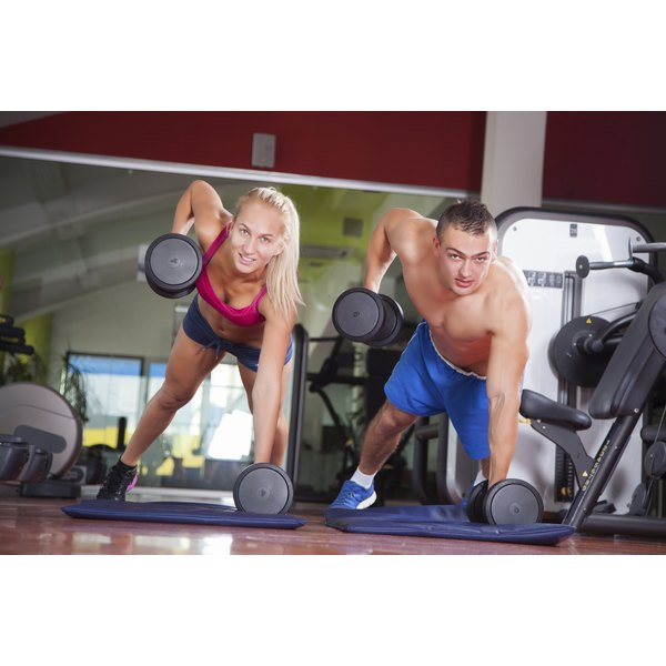 A man and woman are exercising together in a gym.