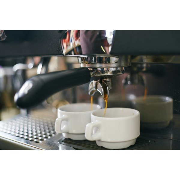 Shots of espresso pouring from a machine.
