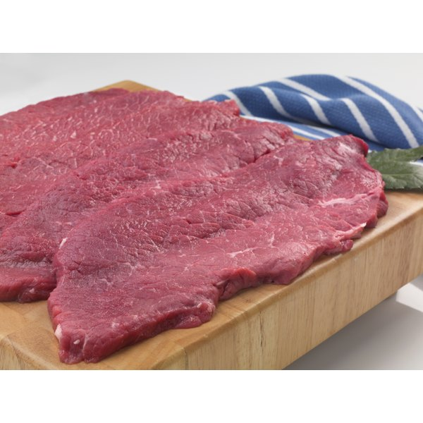 Raw flank steak on a wooden cutting board.