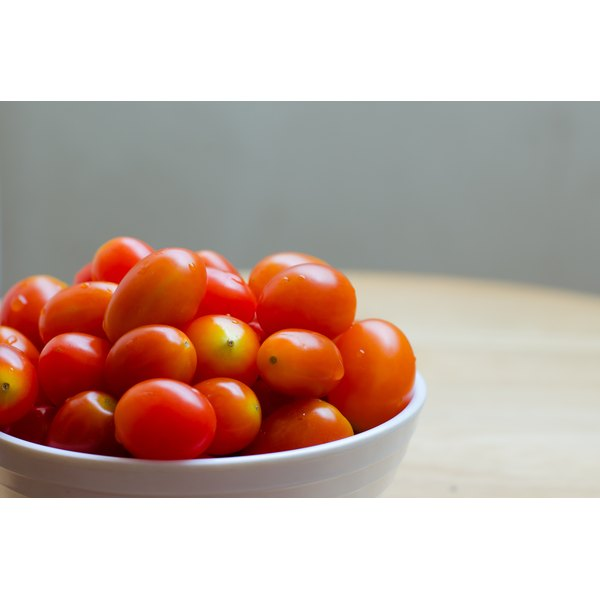 A bowl of cherry tomatoes on a wooden table.
