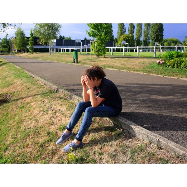 A sad teenager sits on a curb in a park.