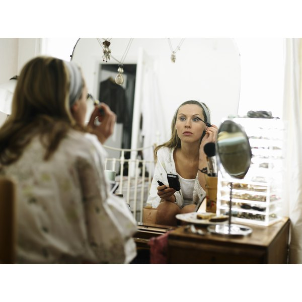 A woman is applying makeup to her face.