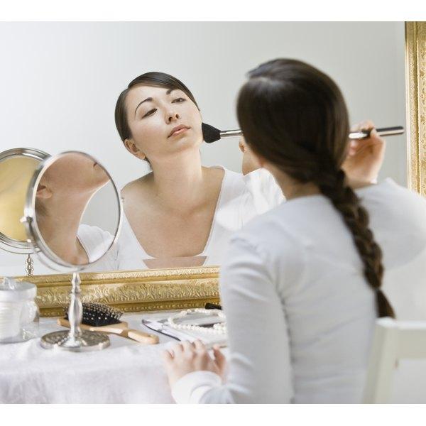 Woman applying makeup in large mirror.