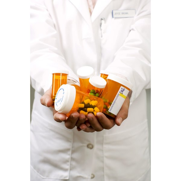 Pharmacist holding prescription medication bottles.