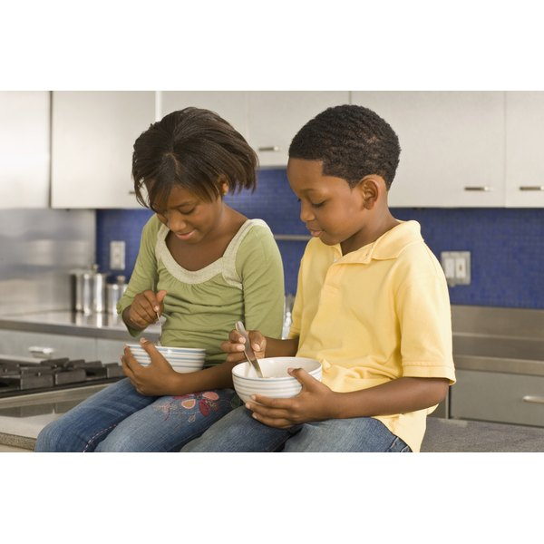 Two young children are eating cereal.