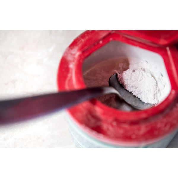 A spoon in a red container holding baking soda.