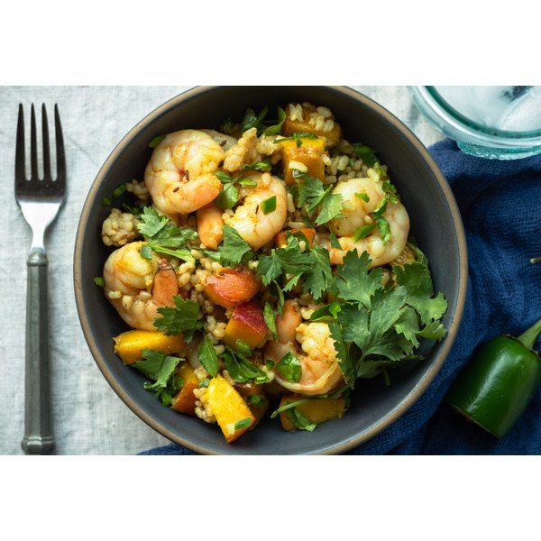 A shrimp and peach risotta topped with fresh cilantro.
