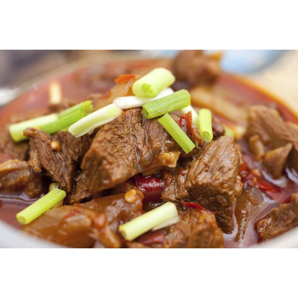 A close up of braised sirloin in a bowl, sprinkled with scallions.