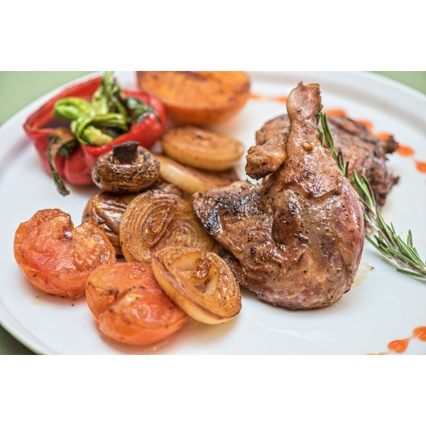 Grillled duck on a plate with grilled vegetables and fresh rosemary.