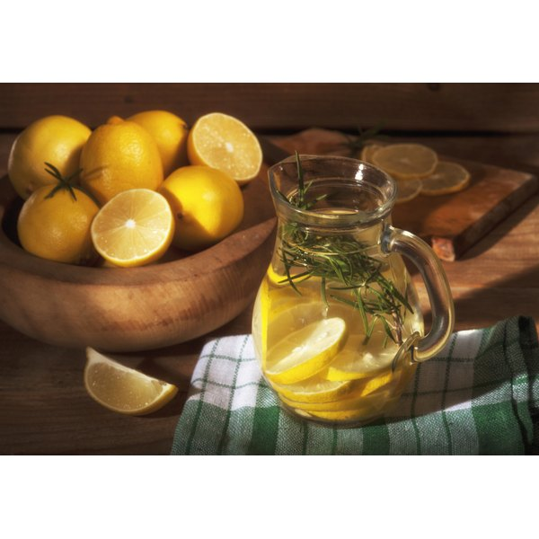 A pitcher of lemon aid with lemons in the background.