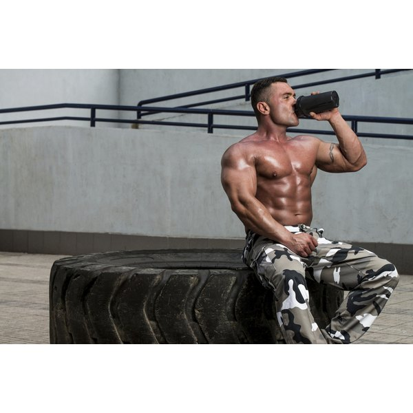 A bodybuilder sits on an oversized tire and drinks a whey-based protein shake.