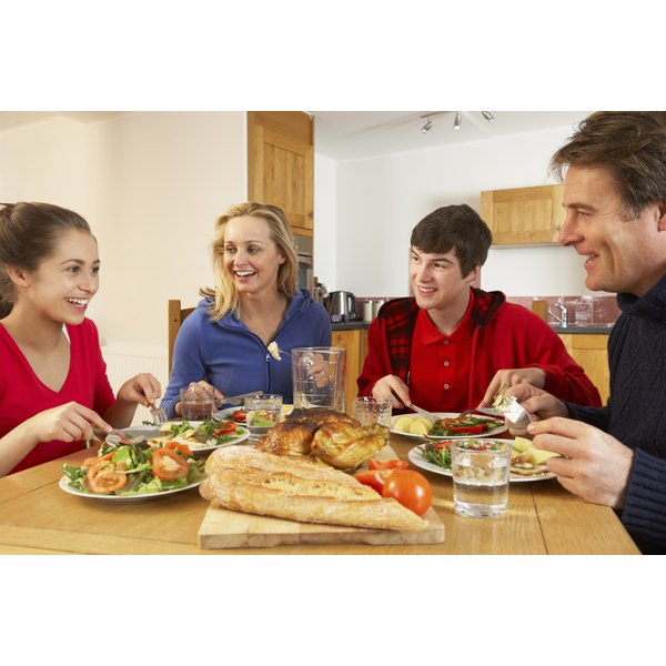 A family of four with two teenage children sit at the kitchen table sharing a healthy meal.