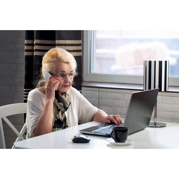 A wealthy elderly lady is on the phone while looking at her laptop computer.
