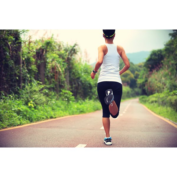 A young woman is jogging on a road.