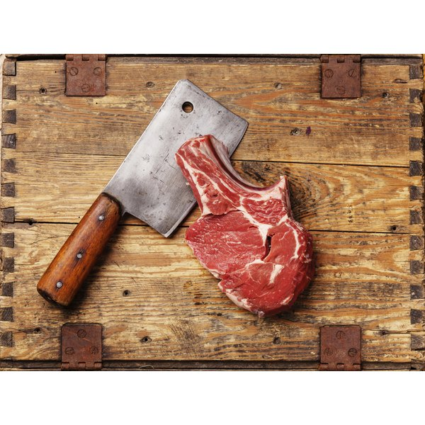 A chopping knife and fresh cut steak on a wooden board.
