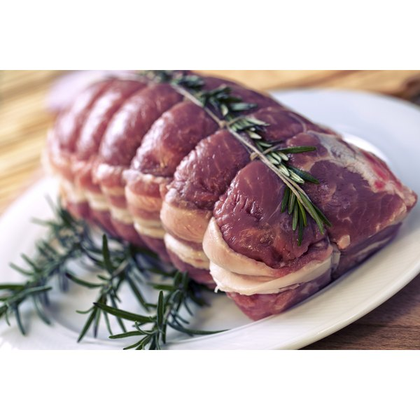 A raw beef roast on a plate with rosemary sprigs.