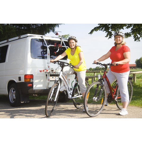 Two overweight women are getting on bicycles.