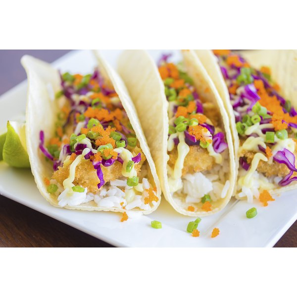 Three fish tacos on a plate.
