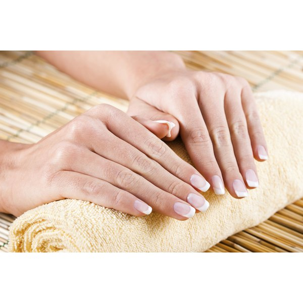 Close-up of healthy looking hands and nails resting on a towel.