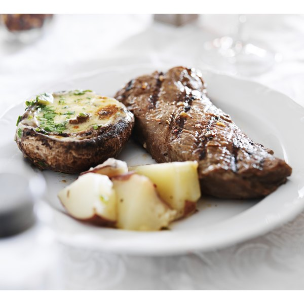 A grilled steak on a plate with potatoes and a stuffed portobello cap.