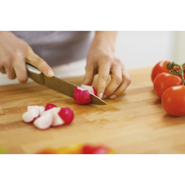 A woman slices radishes on a cutting board.
