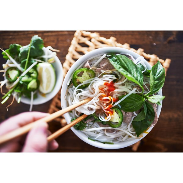 A bowl of Vietnamese pho served with sriracha, chiles, basil and lime.