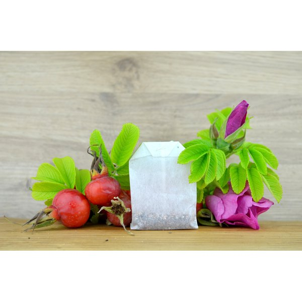 A tea bag with fresh rose hips and petals on a rustic table.