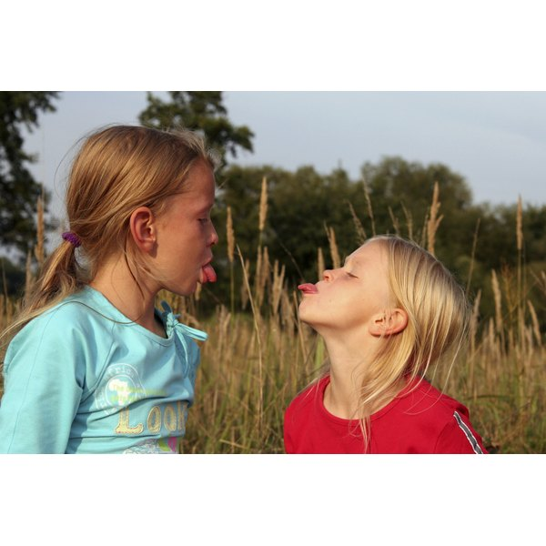 Two young girls stick their tongues out at each other.