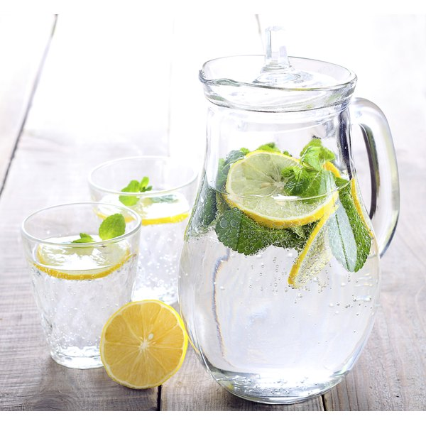 A tall pitcher of seltzer water with lemon slices.