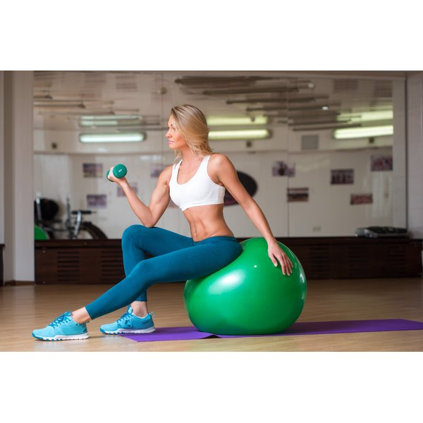 A woman is training on a stability ball.