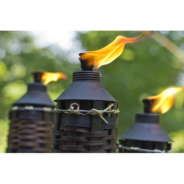 Close-up of three tiki-torches burning citronella in the backyard.