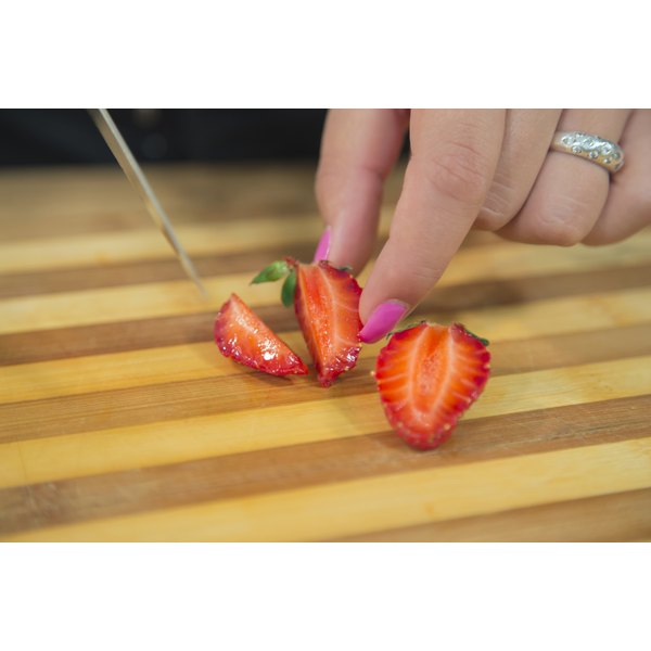 A woman is slicing a strawberry.