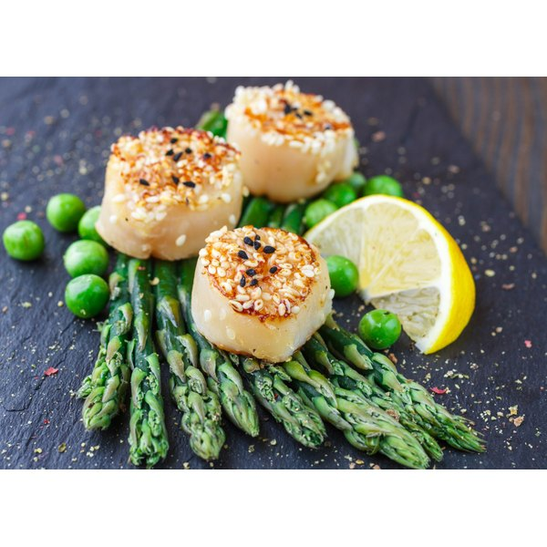 Grilled scallops and asparagus on a board.