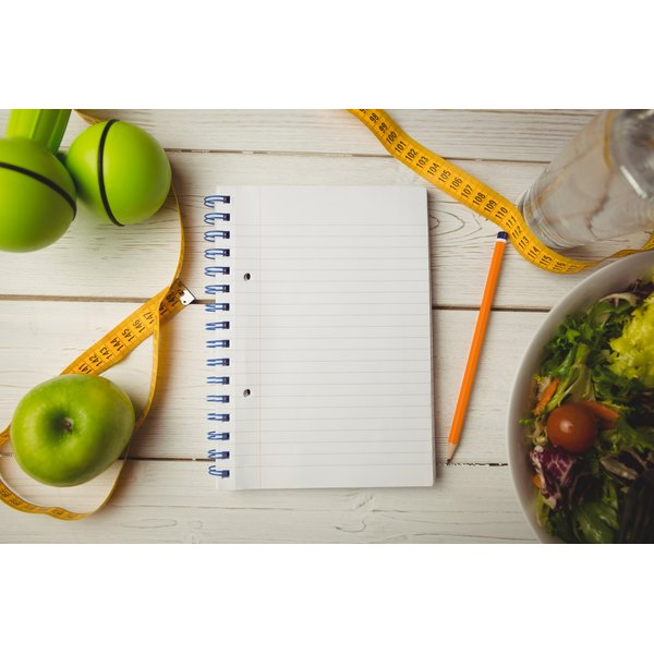 A note pad on a table with a pencil, tape measure and apples.