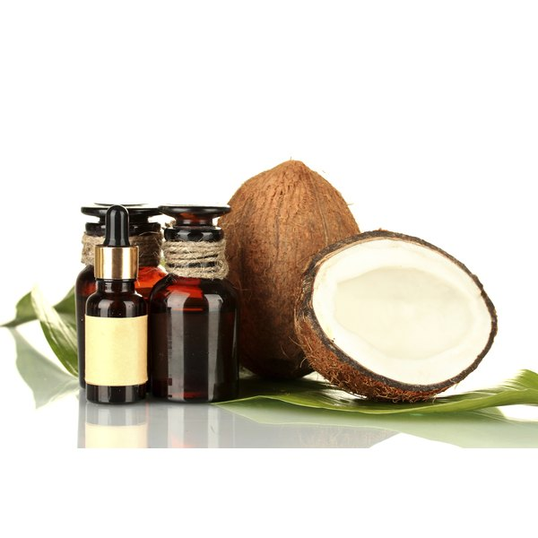 Bottles of coconut oil are seen next to an open coconut half.