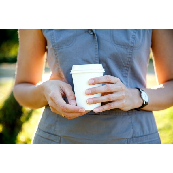 A woman holding a to-go coffee cup.